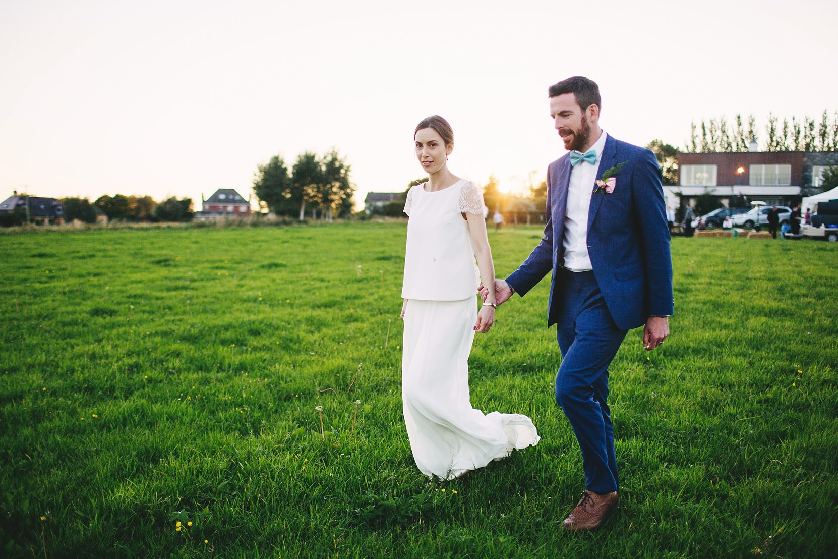 Bride and Groom walking through a field at sunset on a farm in Limerick