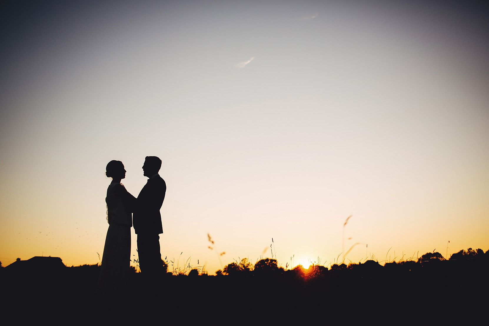 Romantic shot of a bride and groom in a beautiful setting at sunset