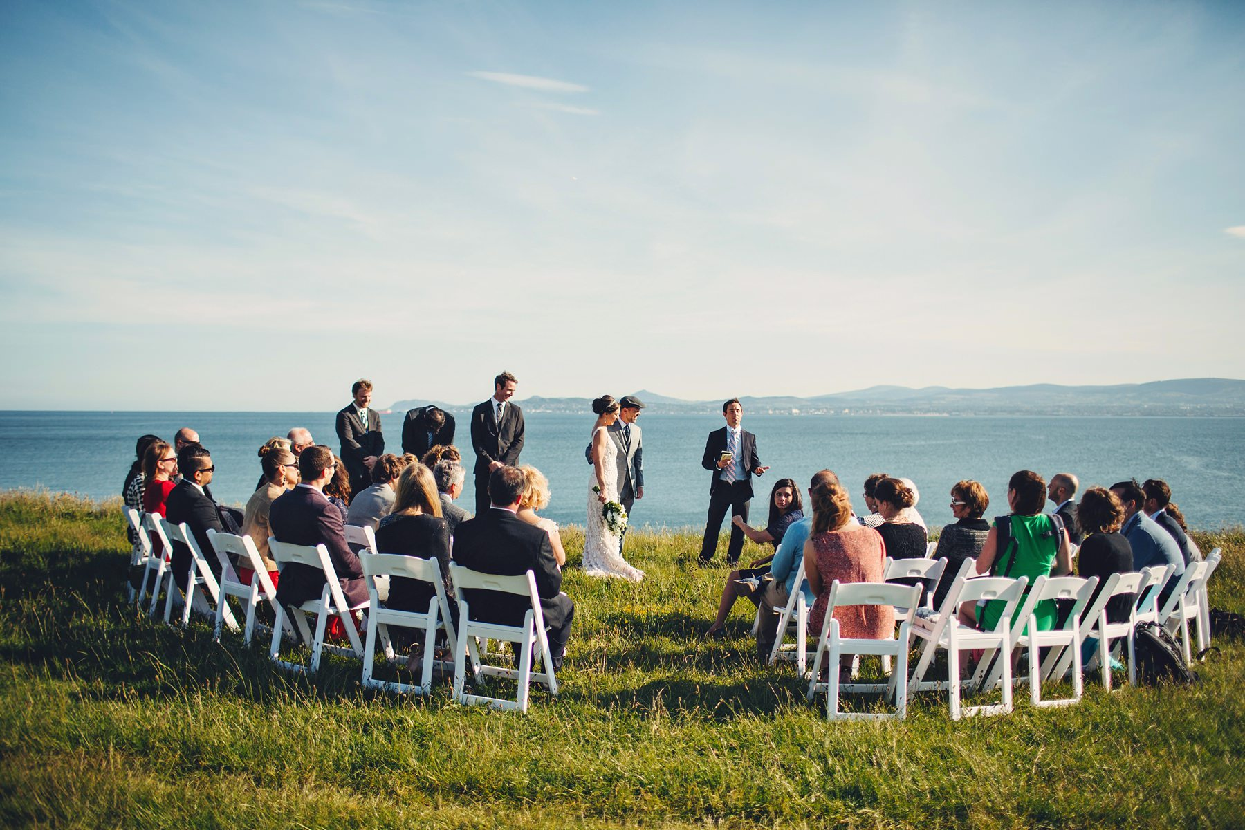 A wedding photo of a bride and groom and their guests on a cliff side at Martello tower in Dublin.
