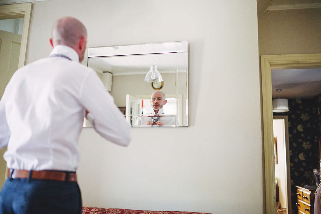 Groom looking in the mirror on the wedding morning