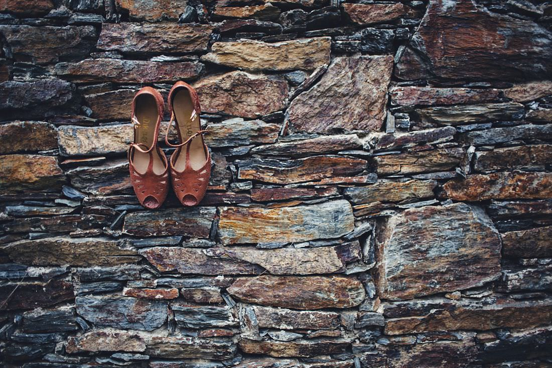 Wedding shoes pictured in a stone wall.