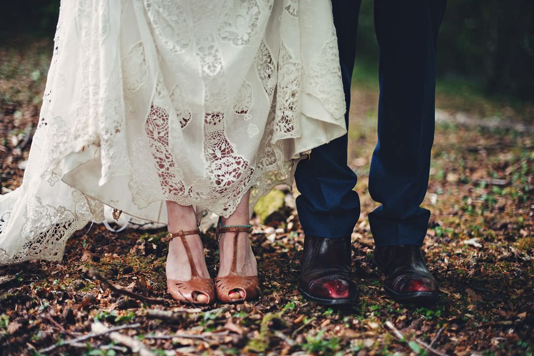 bride and grooms feet in the woods