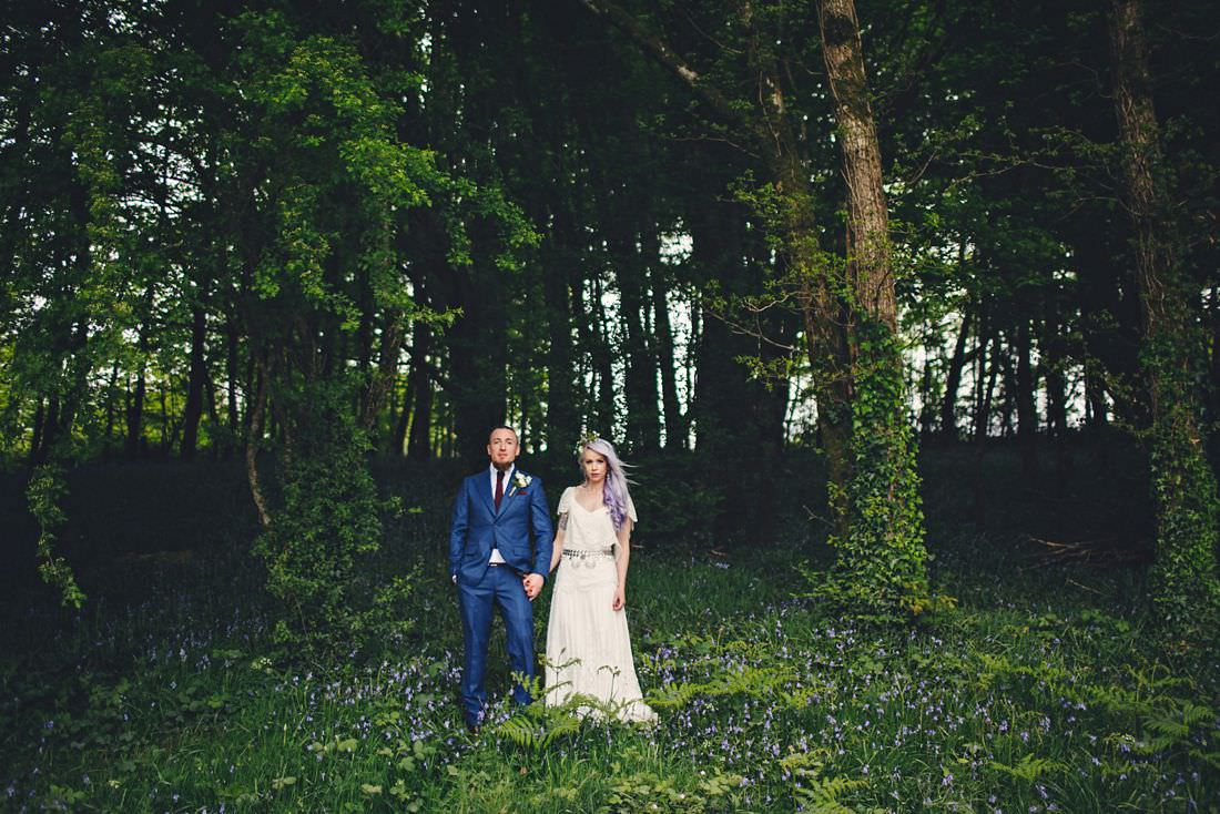 bride and groom in the woods holding hands