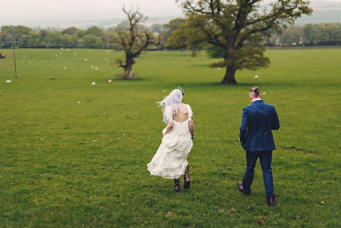 bride and groom walking through a field shot from behind