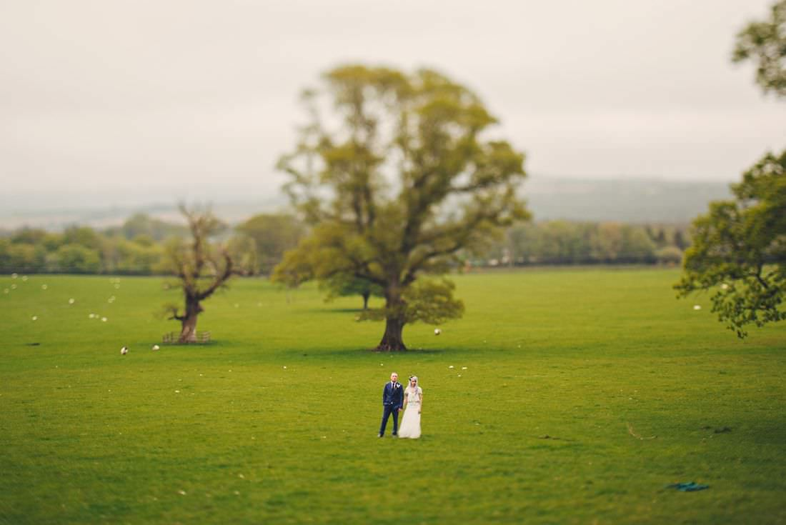 bride and groom standing in front of a tree in a field