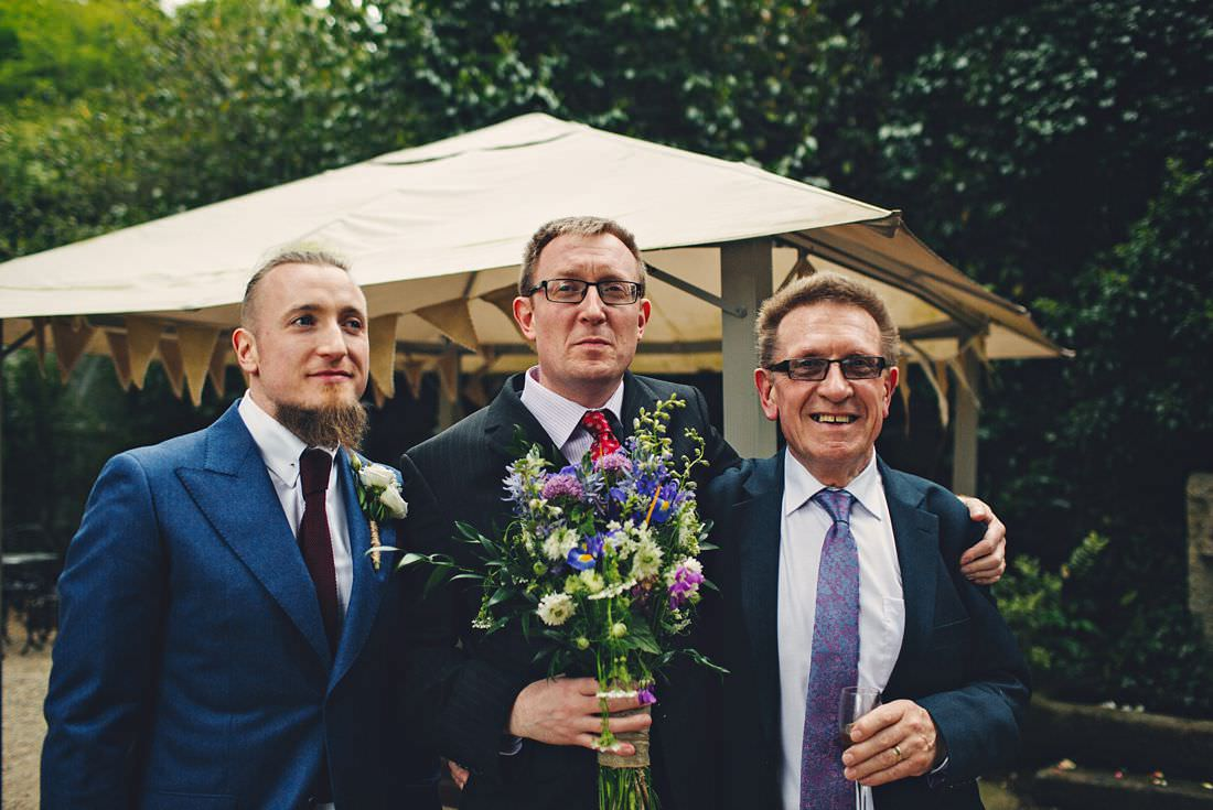 three men with a bouquet at a wedding