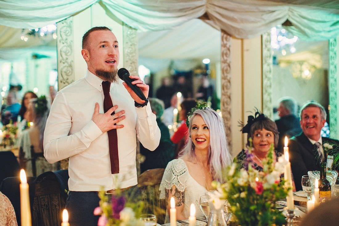 the groom making a speech at a wedding with his jacket off