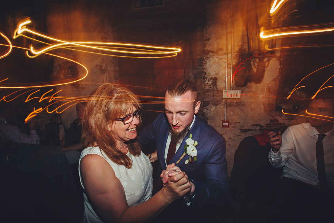 groom dancing with a lady at his wedding