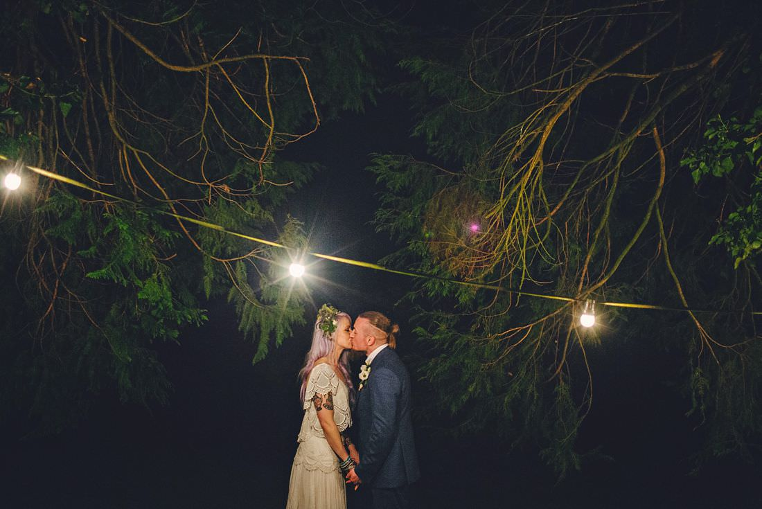 bride and groom kissing under a light at their wedding
