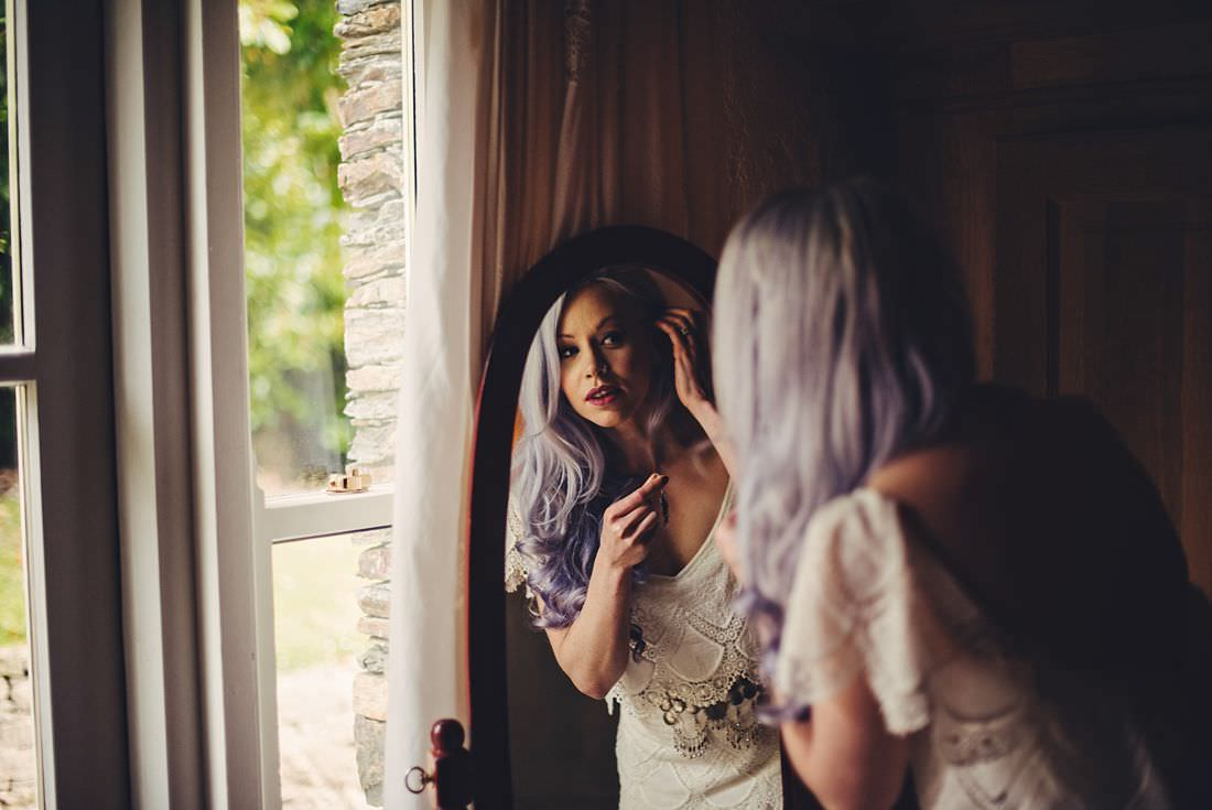 Bride looking in the mirror putting on her earrings