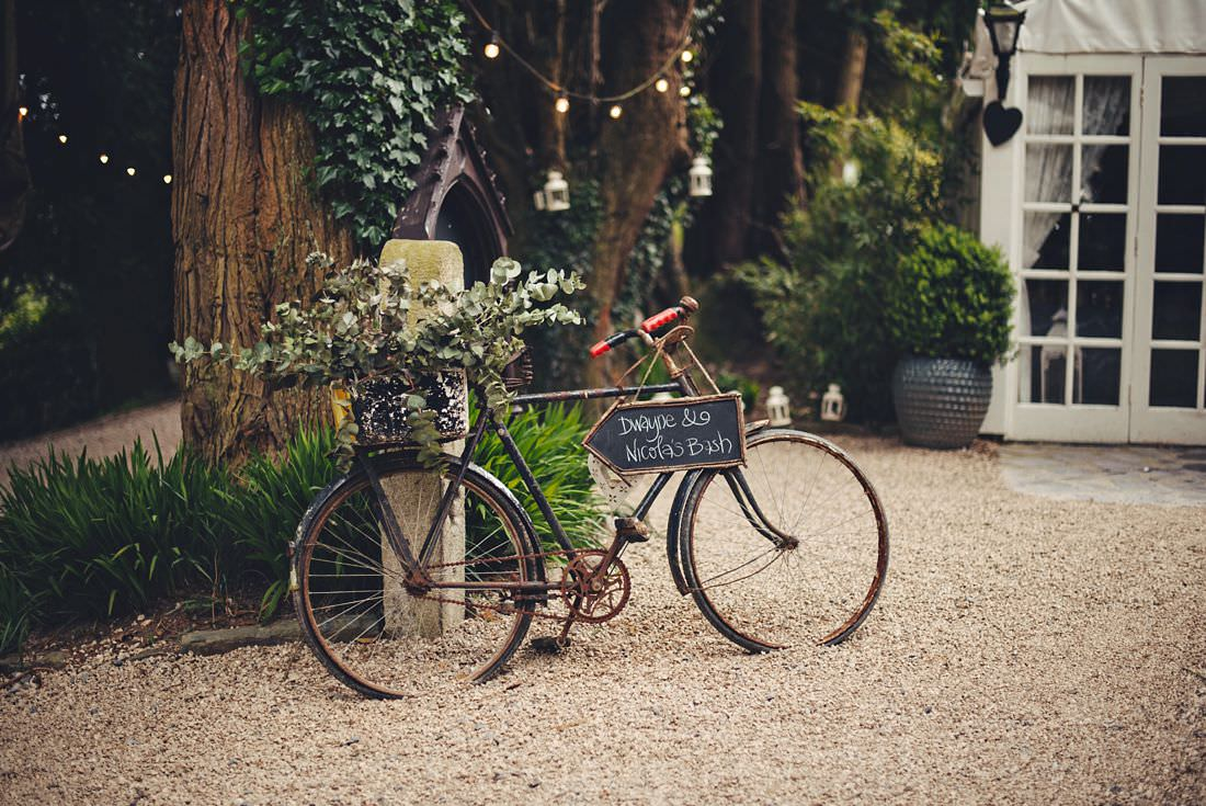 an old bike agains a wall at a wedding