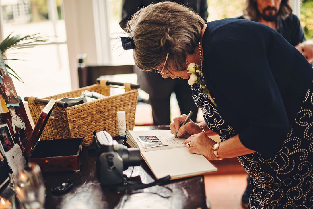 a lady signing a book at a wedding
