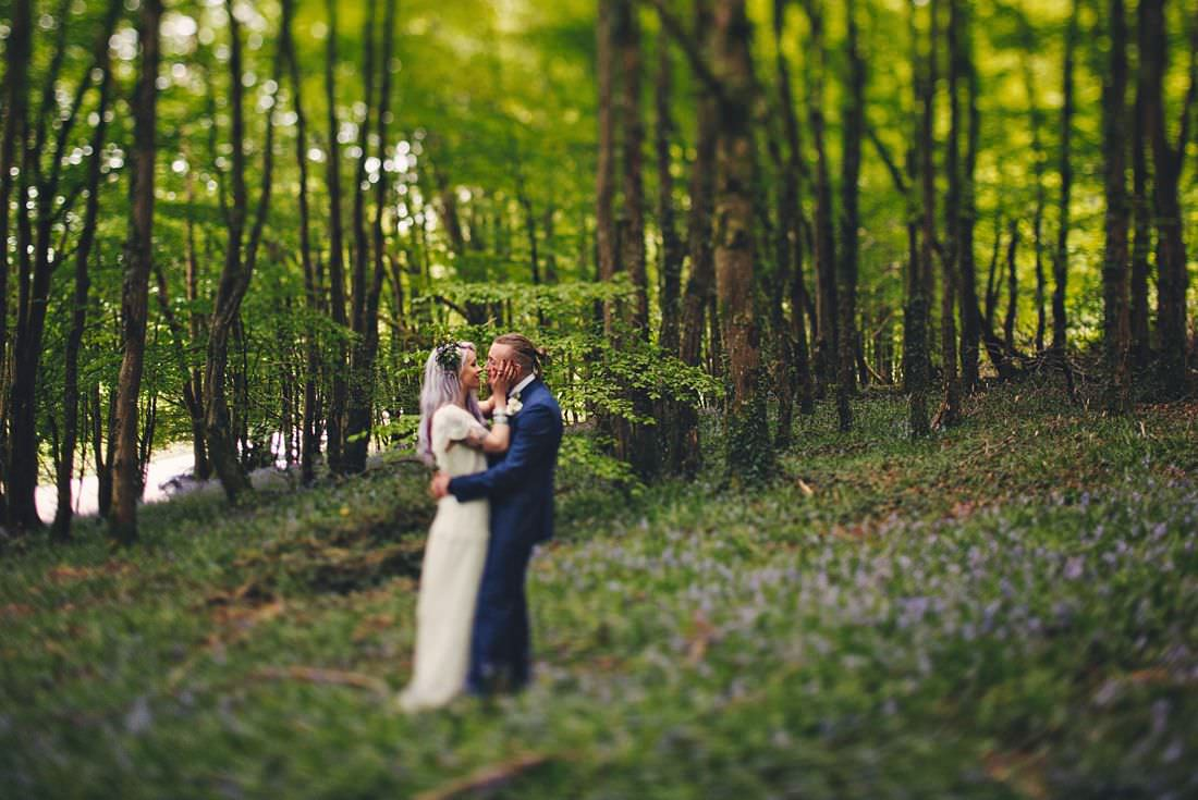 bride and groom in bluebells kissing