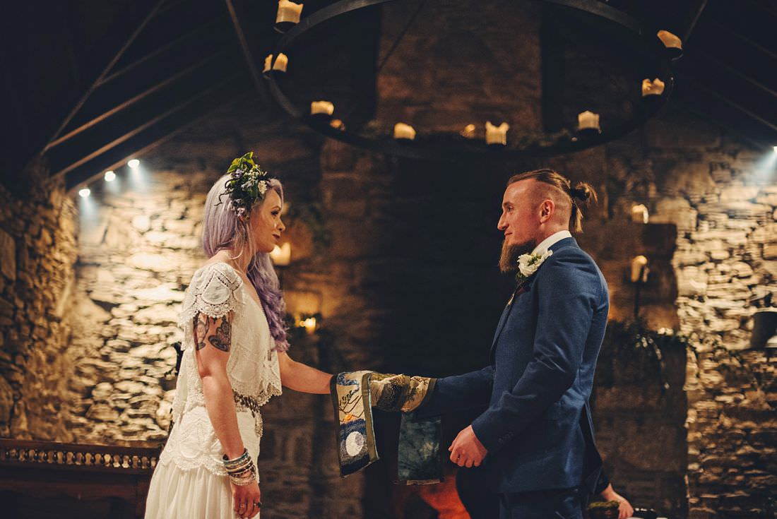 Bride and groom performing a hand fasting during a wedding ceremony