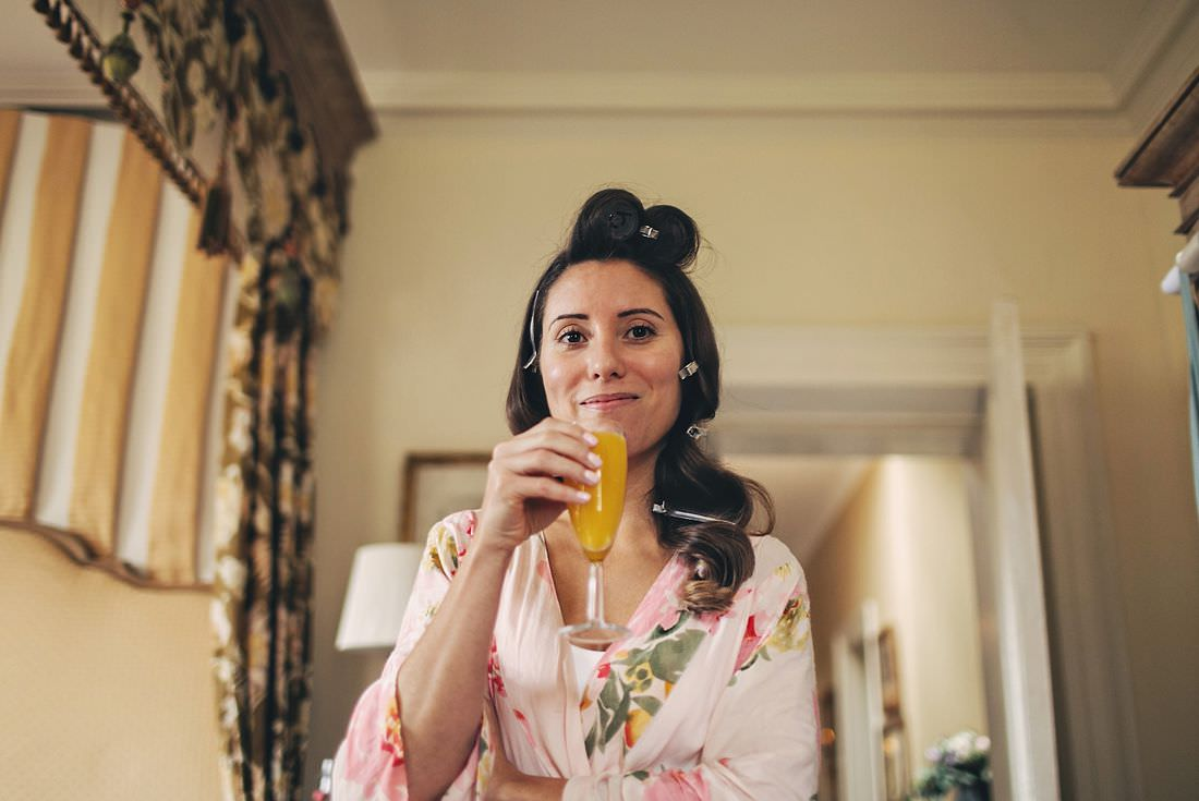 A bride drinking a glass of champagne