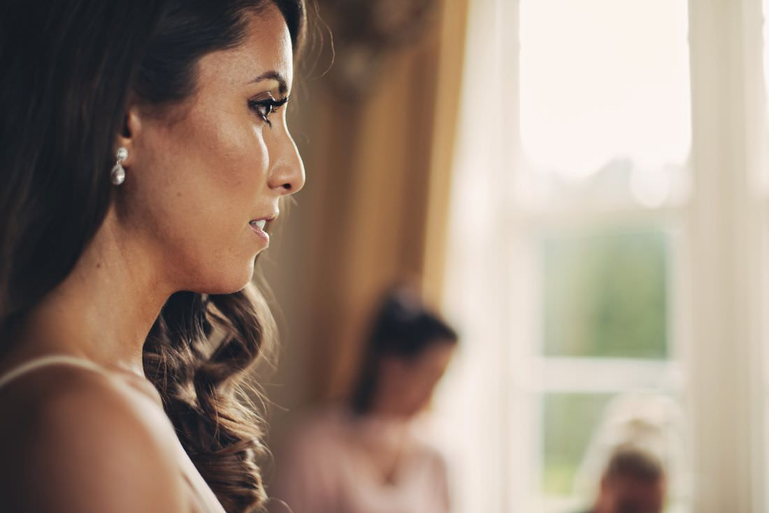 close up of a bride from the side looking in a mirror at lisnavagh house for a wedding