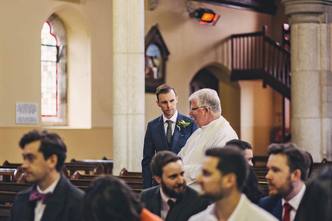 a priest talking to the groom