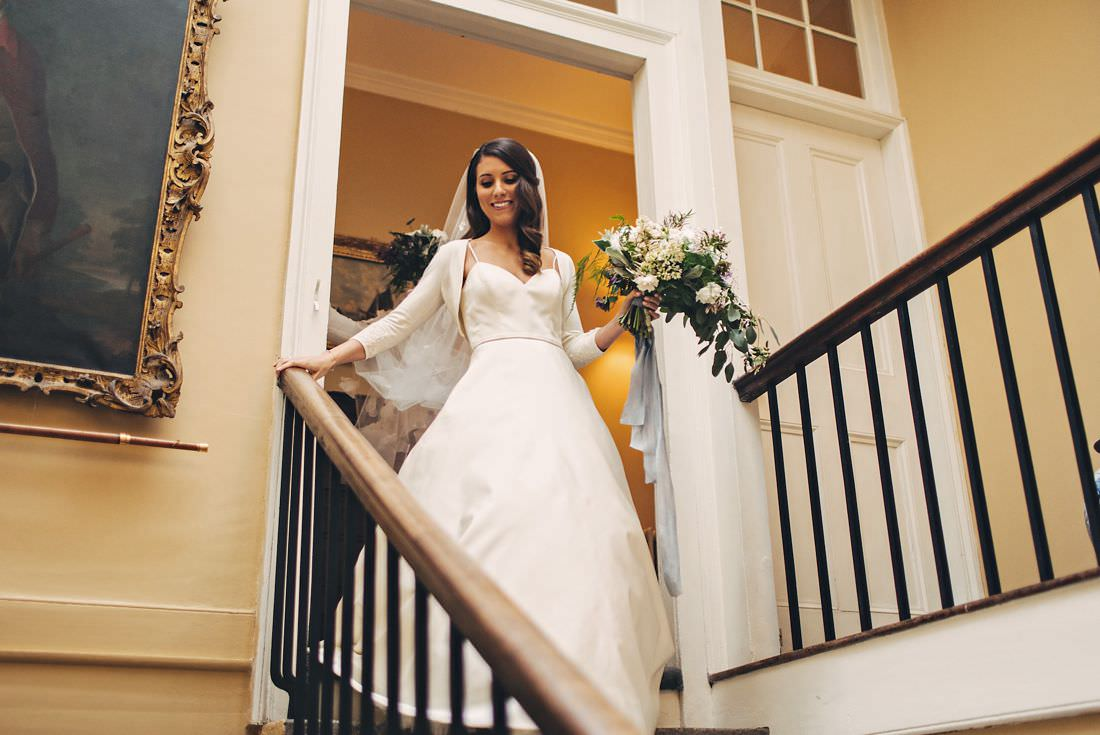 bride coming down a stairs holding bouquet
