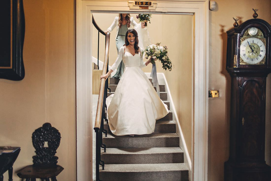 bride coming down the stairs in her dress