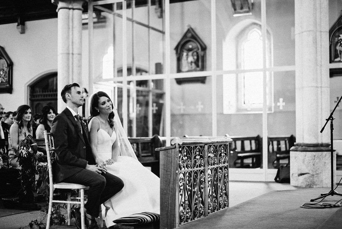 bride and groom sitting at the front of the church in black and white