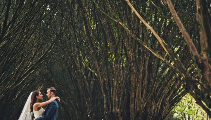 Bride and groom in the woods with trees each side