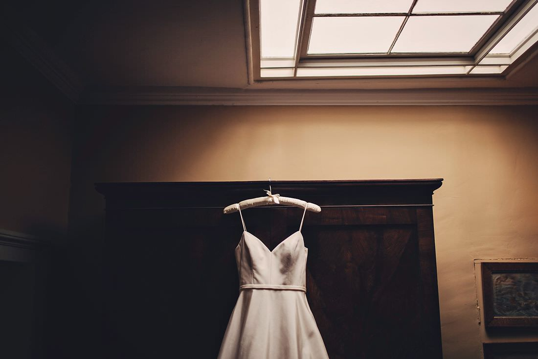 A wedding dress hanging in some nice light
