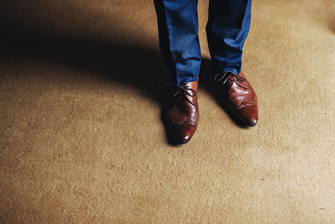 a picture of a guys feet with brown shoes on and blue trousers