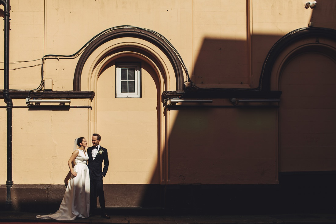 Bride and groom in the city shadows