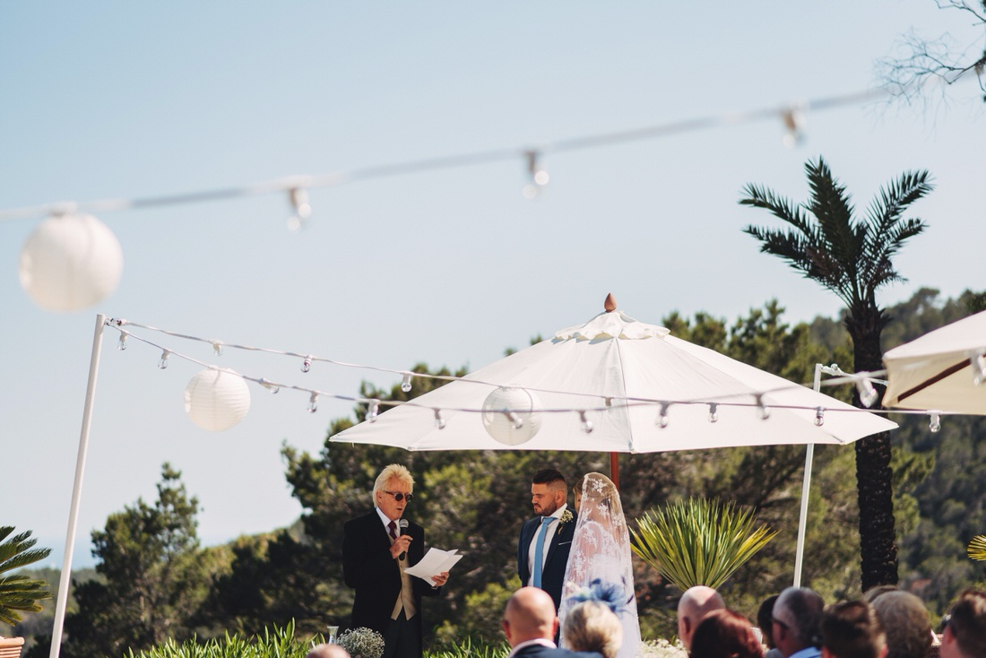 Bride and groom under an umbrella at their Spain wedding