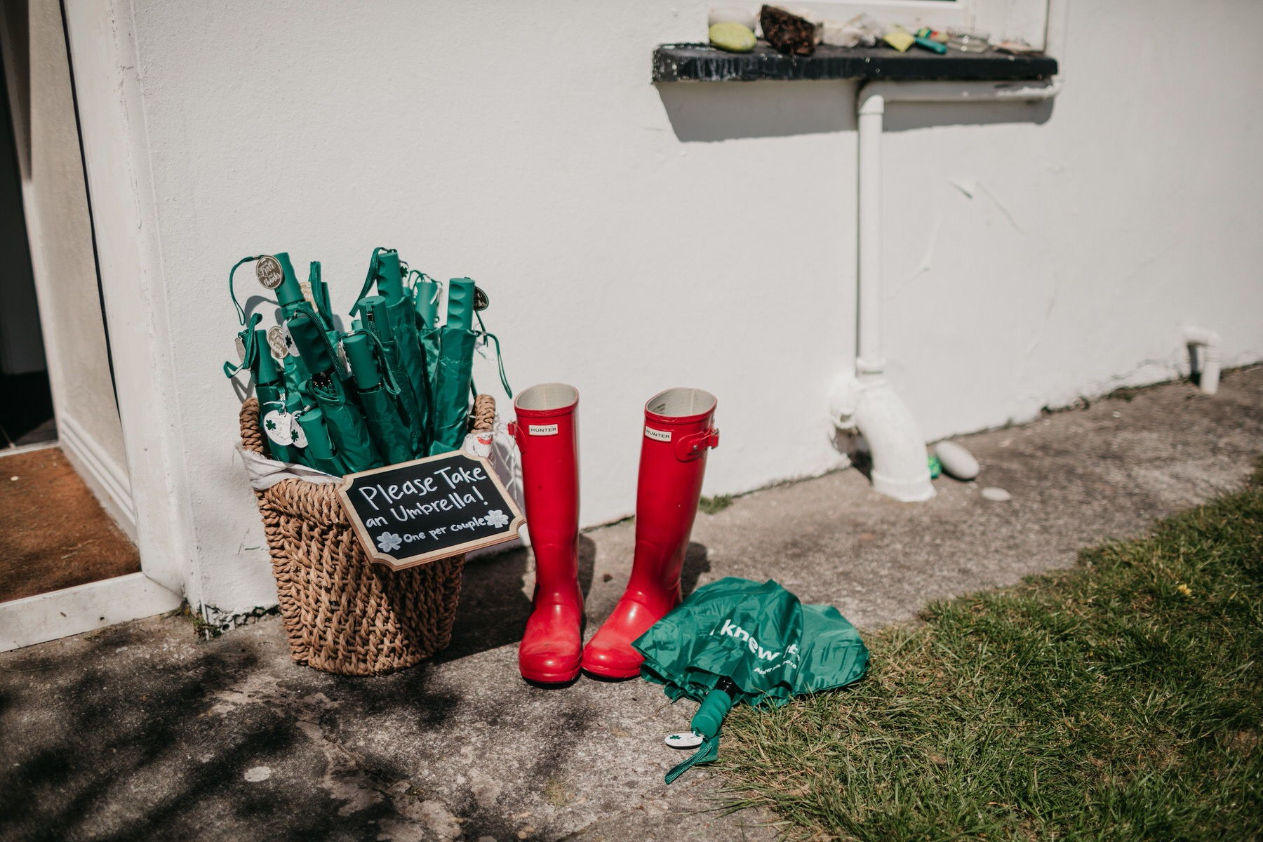 Boots and umbrellas laid out for a wedding