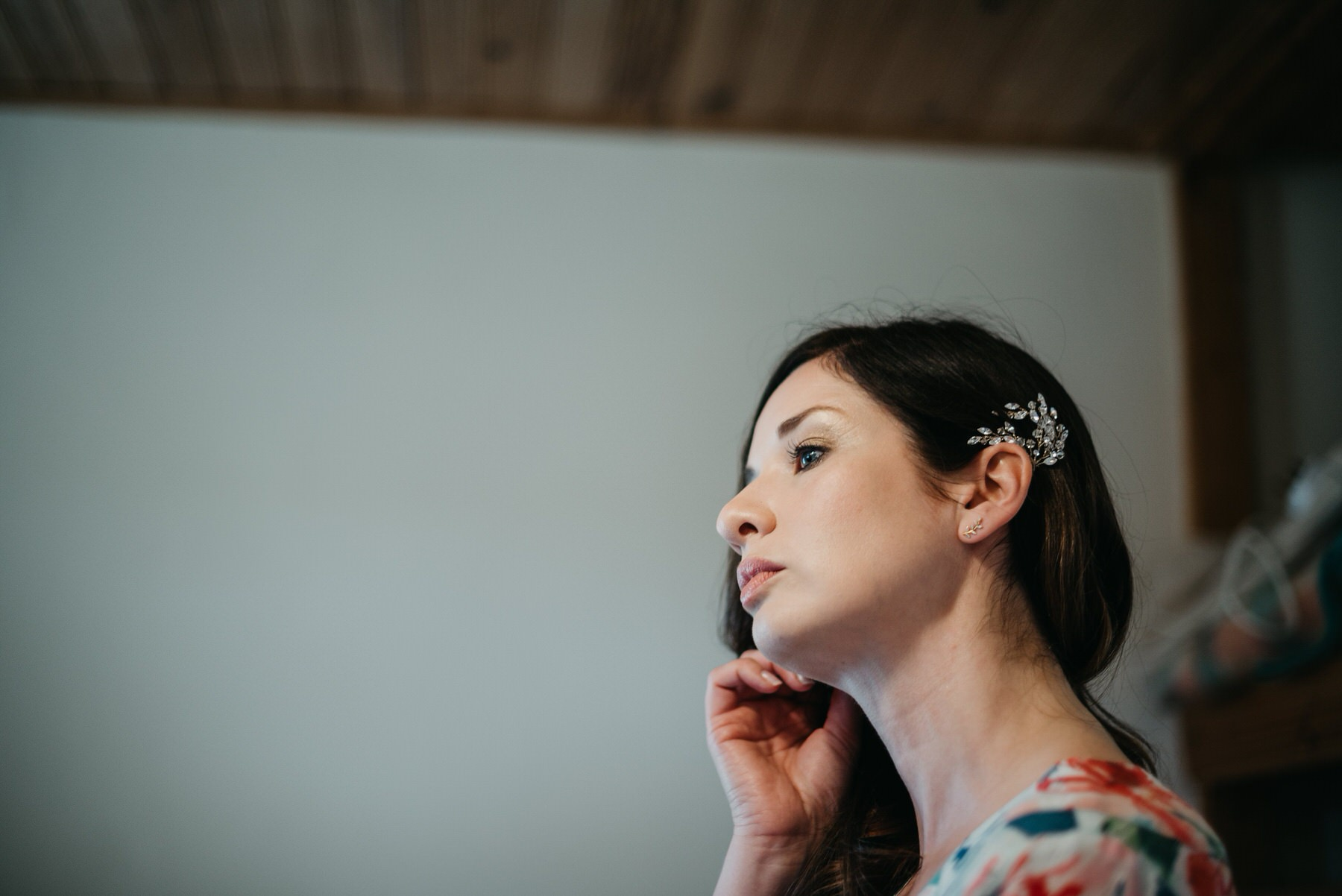 Side view of the bride doing her makeup