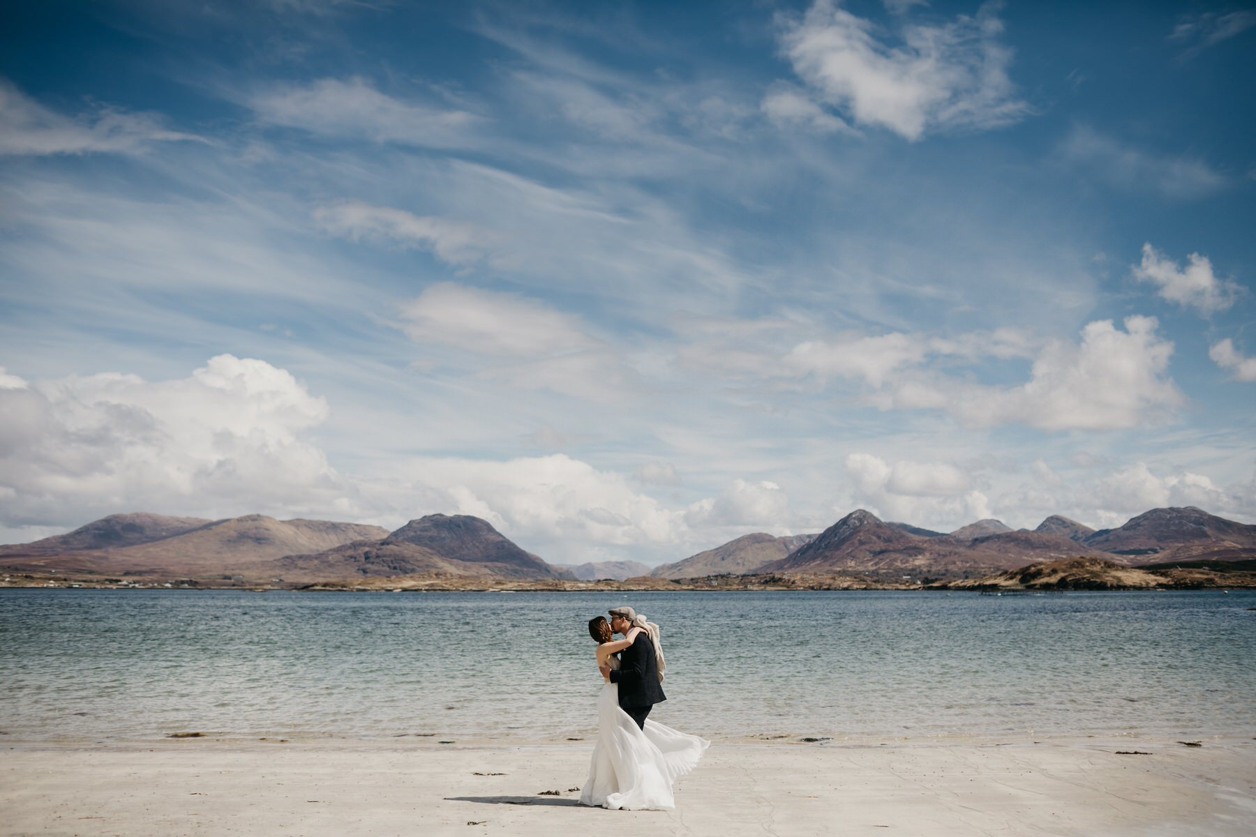 A bride and groom kissing on the beach