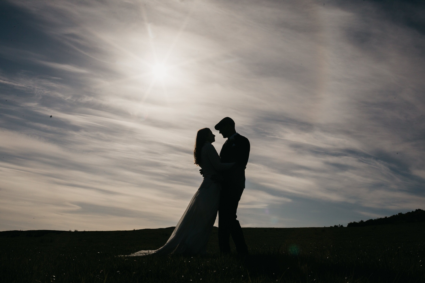 Silhouette of the bride and groom against the sky
