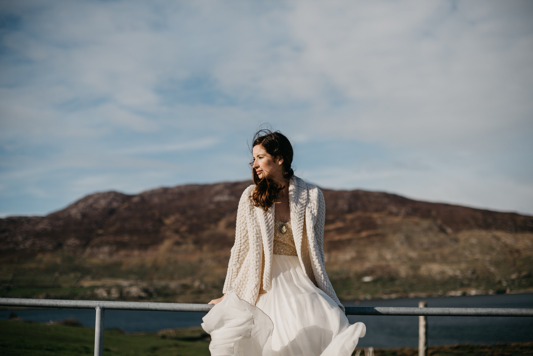 Bride sitting on a fence in the wind