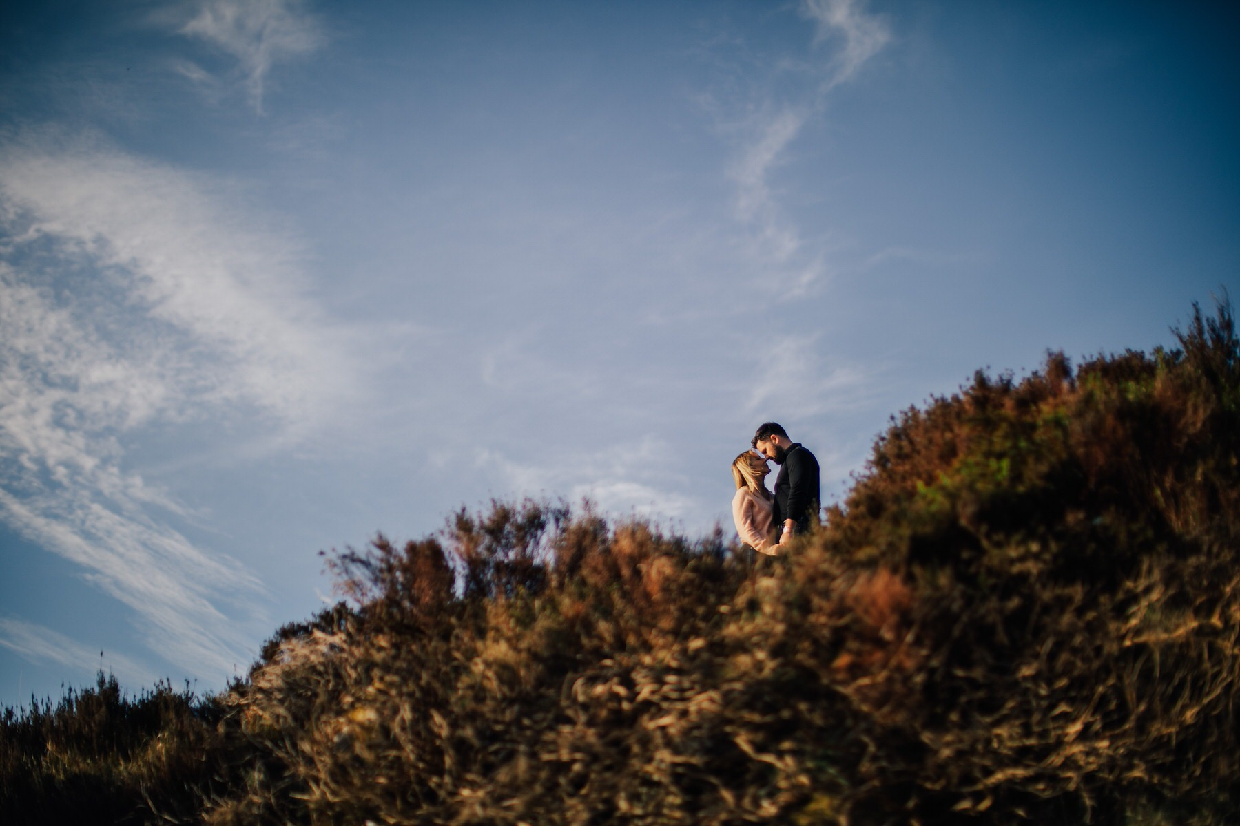 a couple hugging on a mountain top