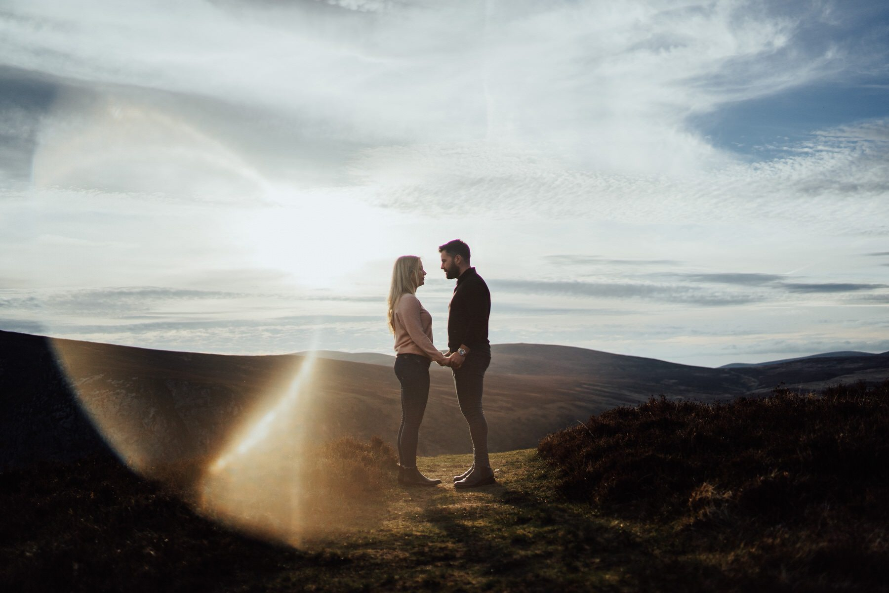 A couple holding hands on a mountain with sun flare hitting a camera