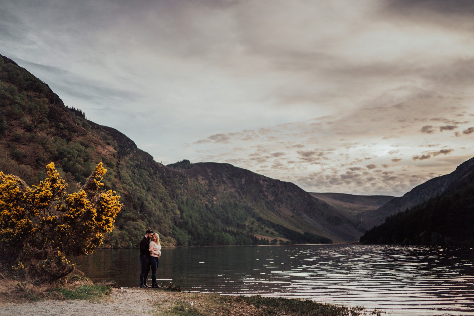 A couple posing by the water at Glendalough