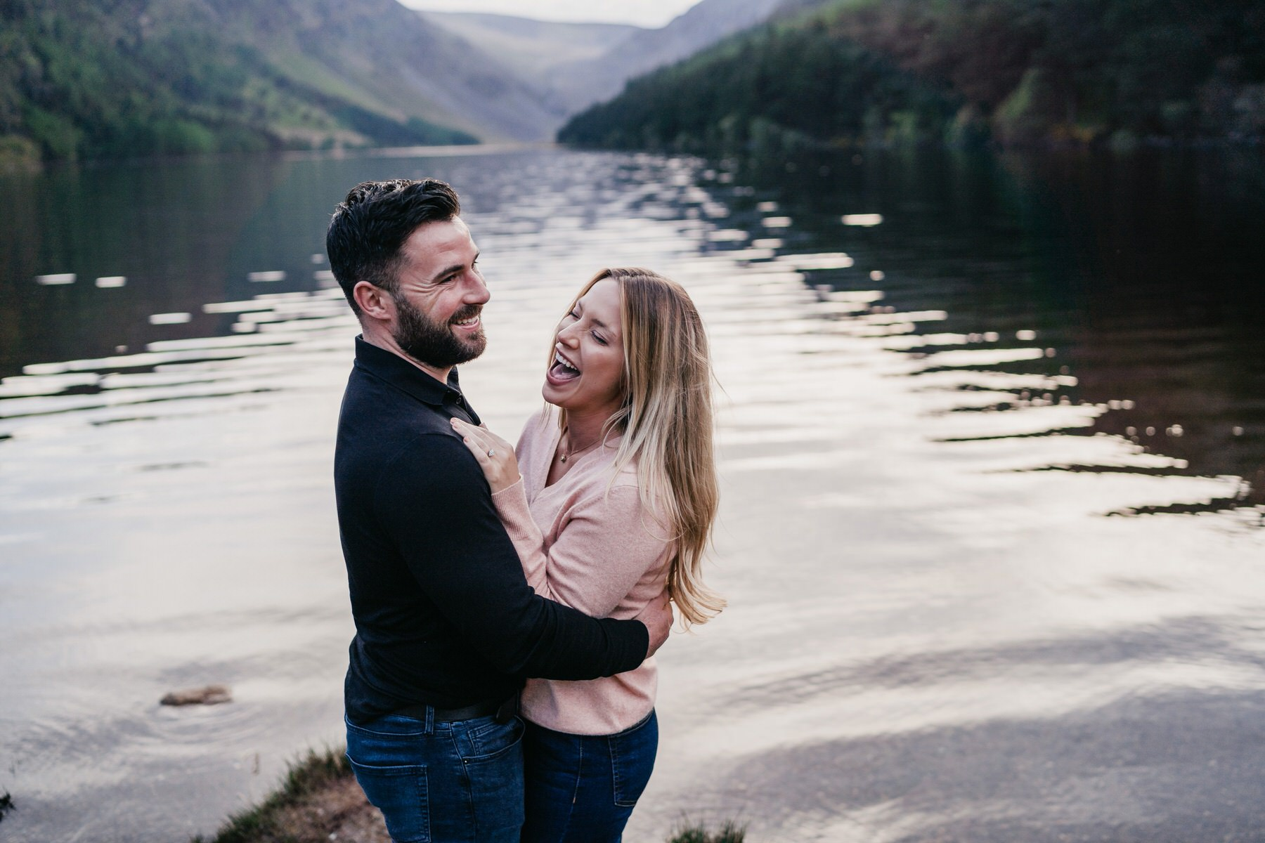 A couple laughing by the water at Glendalough