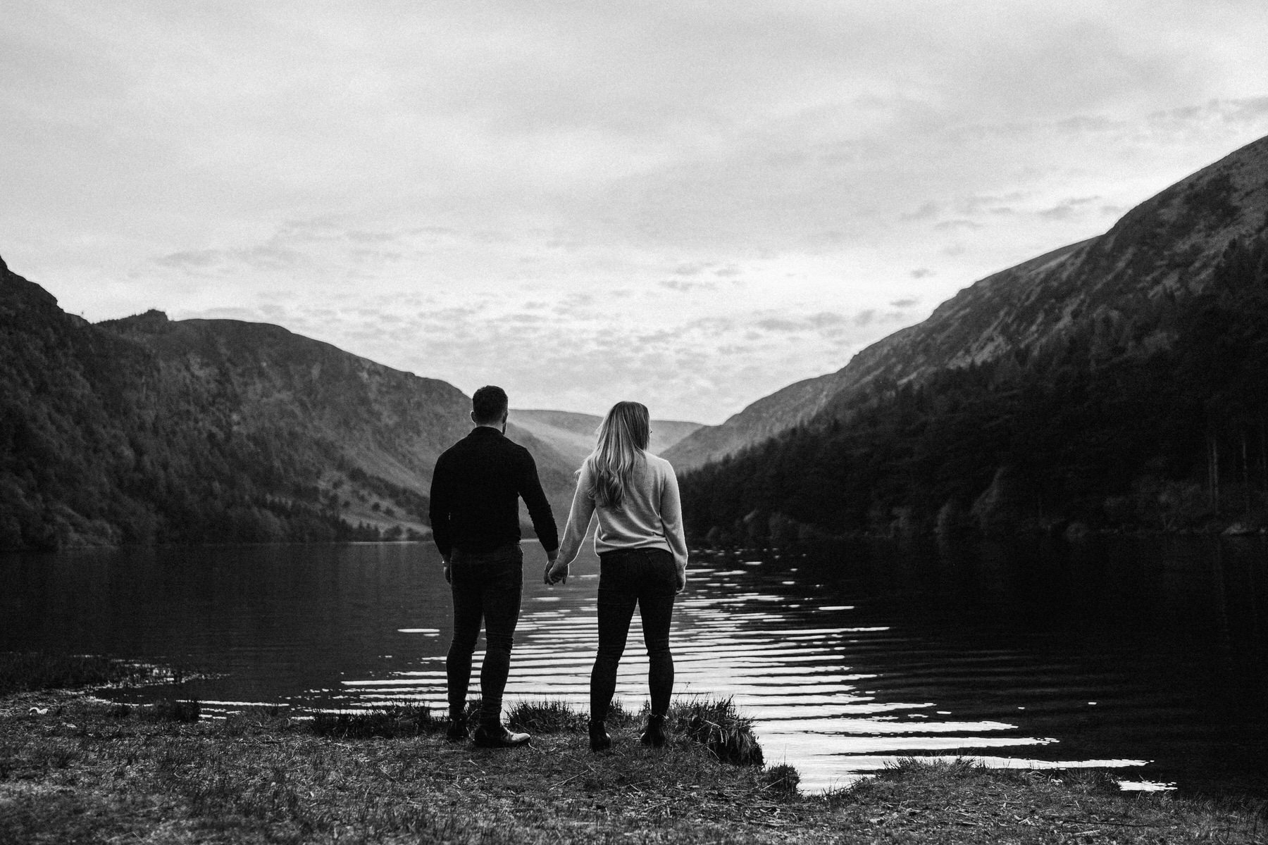 couple holding hands looking out over a lake
