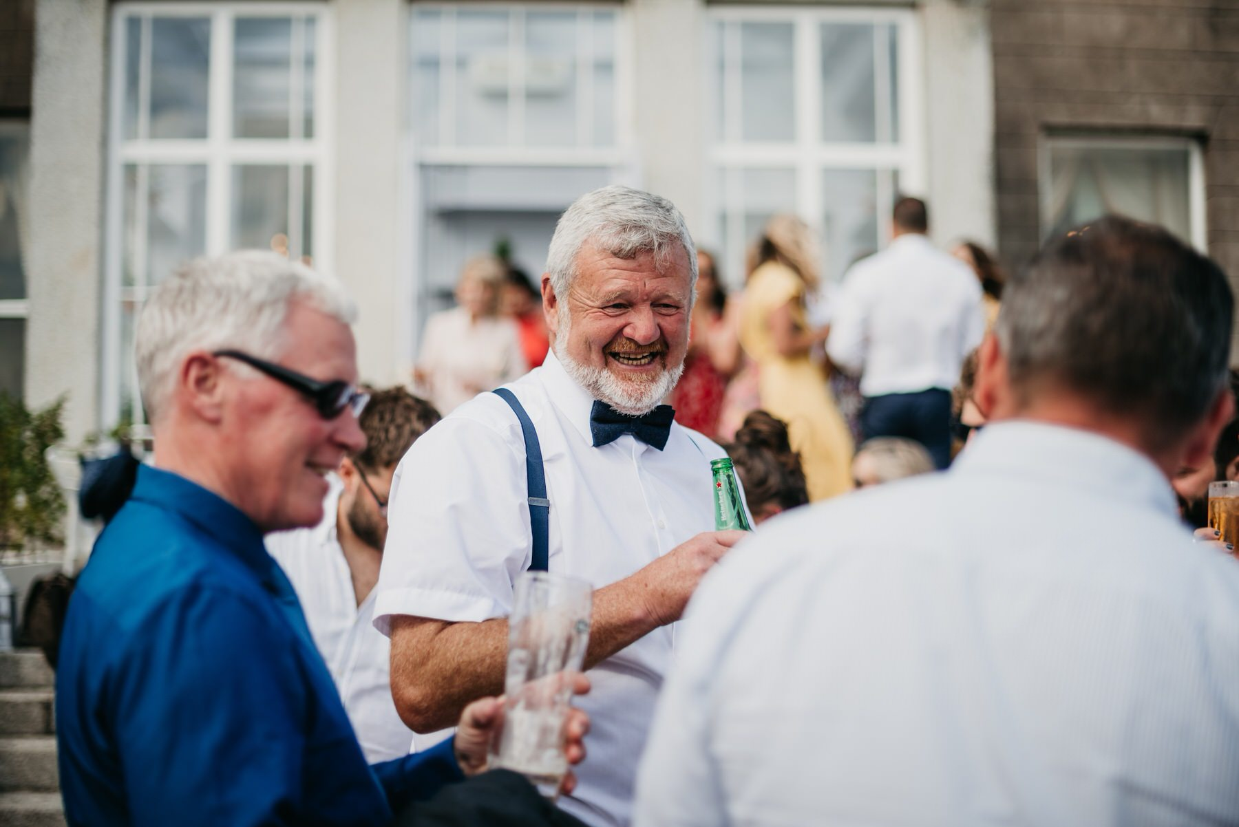 man enjoying a drink at a wedding