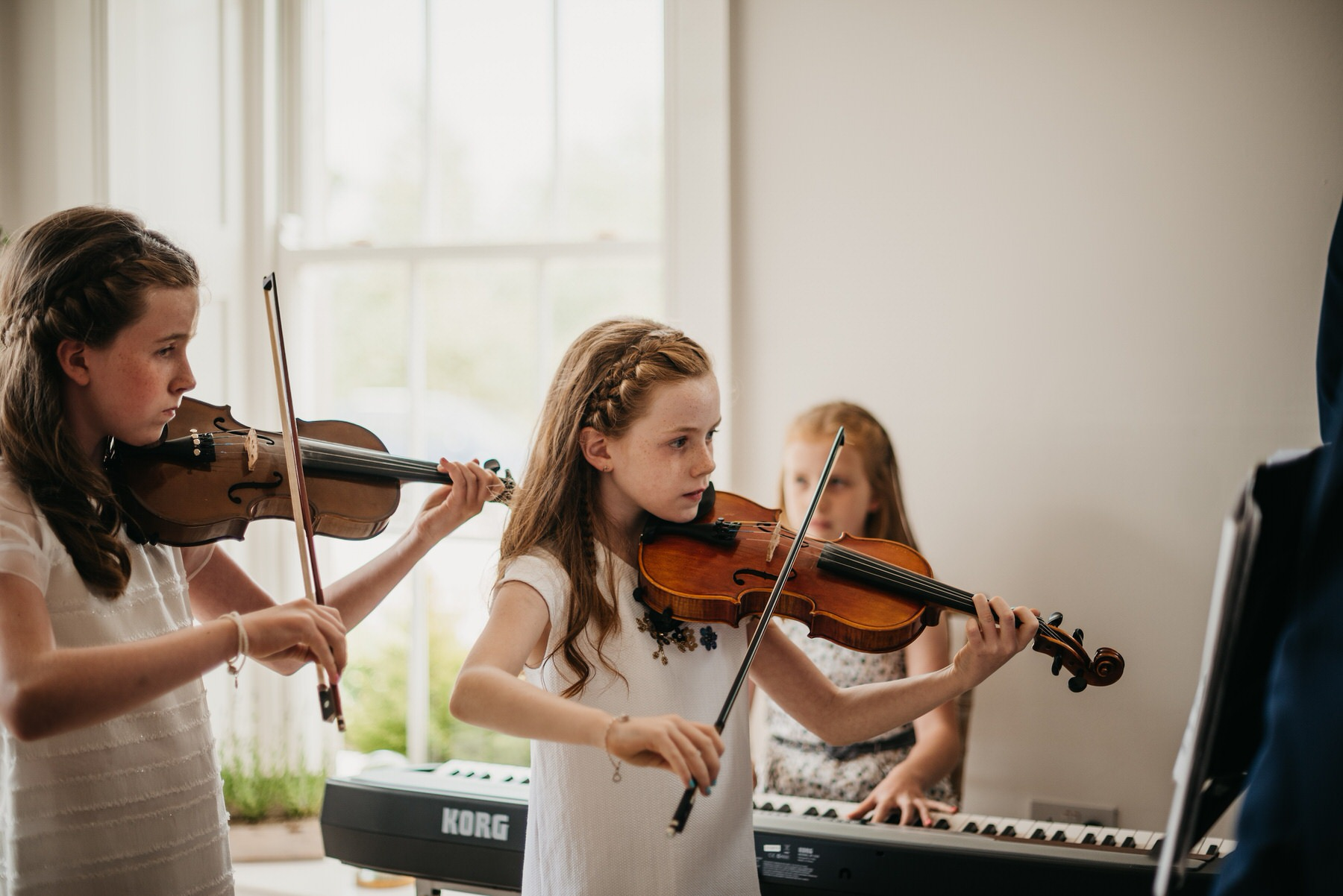 girls playing violin at a wedding